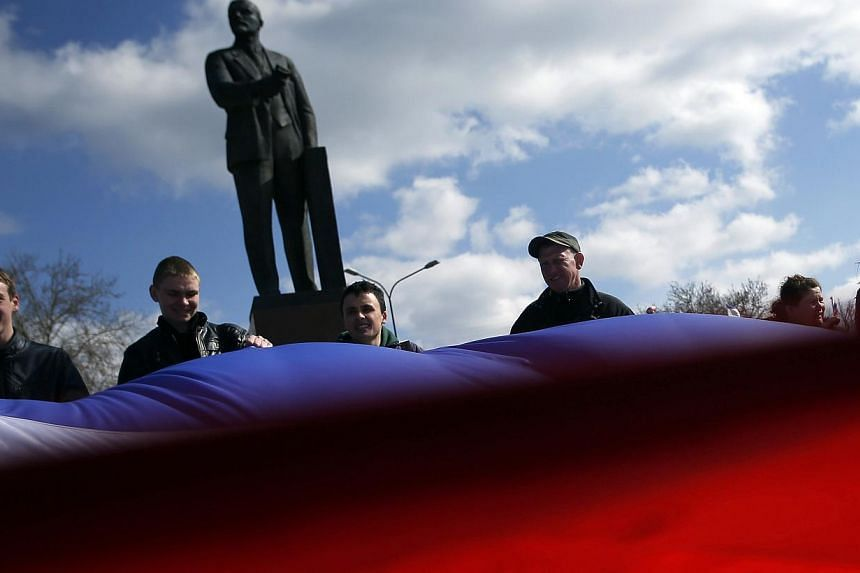 People hold a Crimean flag in front of Lenin's statue in the centre of Simferopol on March 18, 2014.Russian border guards have stepped up checks on goods entering from Ukraine, officials from the customs services and an agricultural inspection