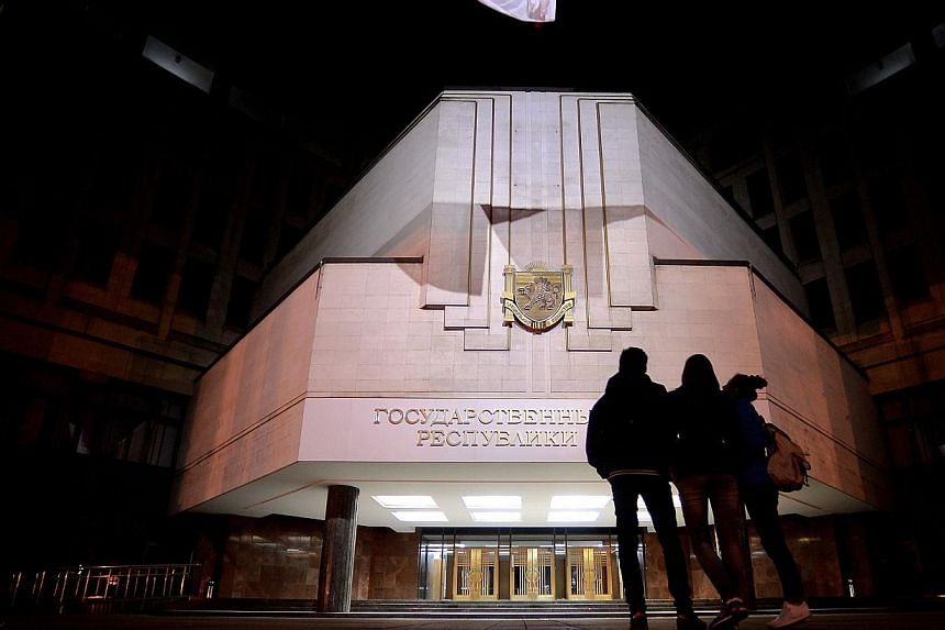 """People stand in front of the Crimean parliament bearing the new sign reading """"State council of Crimean Republic"""" in central Simferopol on March 18, 2014.Russia will not bail out companies who may face financial difficulties, Finance Minister An"""