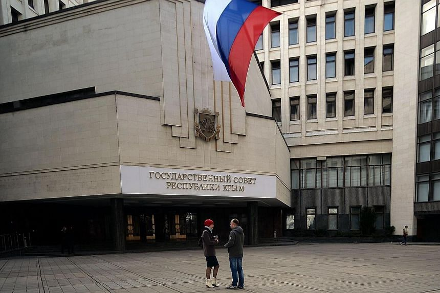 People stand under a Russian flag in front of the Crimean parliament bearing a new sign reading State council of Crimean Republic in central Simferopol on Thursday, March 20, 2014. Ukraine's ambassador to the United Nations in Geneva warned on T
