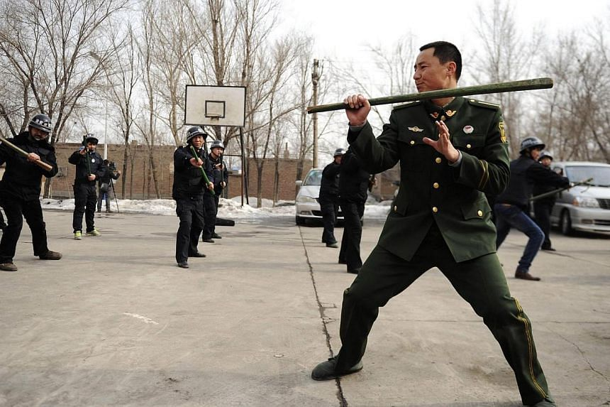 """A paramilitary policeman demonstrates for officers during a security drill in Urumqi, Xinjiang autonomous region on March 18, 2014.China will improve military training to reach """"combat standard"""", state media said on Thursday, March 20, 2014, as"""