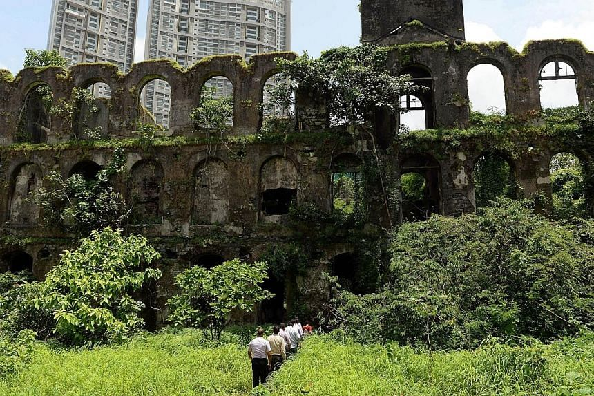In this photograph taken on August 27, 2013, Indian forensic officials enter The Shakti Mills Area in Mumbai, the scene of a gang rape on a female photojournalist.A Mumbai court convicted four men on Thursday, March 20, 2014, over the gang rape
