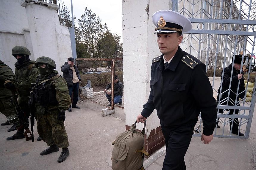 A Ukrainian officer leaves as Russian soldiers stand guard after they took control of the Ukrainian navy south headquarters base in Novoozerne on March 19, 2014. -- PHOTO: AFP