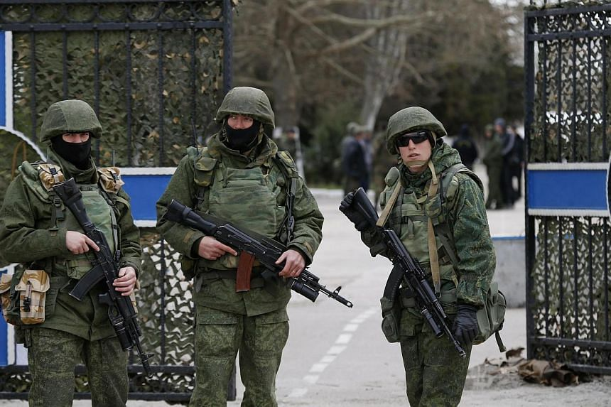 Armed men, believed to be Russian servicemen, stand guard outside the naval headquarters after it was taken over by pro-Russian forces in Sevastopol, on March 19, 2014. Russian forces took control of another Ukrainian naval base in Crimea late on Wed