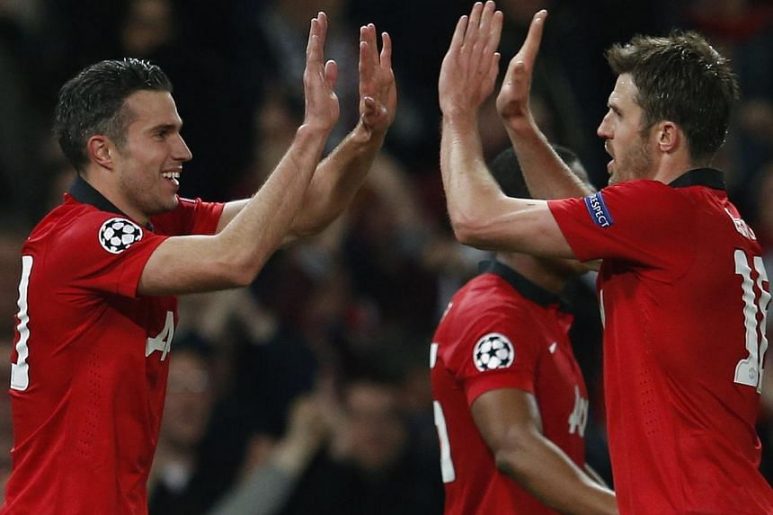 Manchester United's Robin van Persie (left) celebrating with teammate Michael Carrick after the Dutch Striker's second goal against Olympiakos during their Champions League match at Old Trafford on March 19, 2014. -- PHOTO: REUTERS