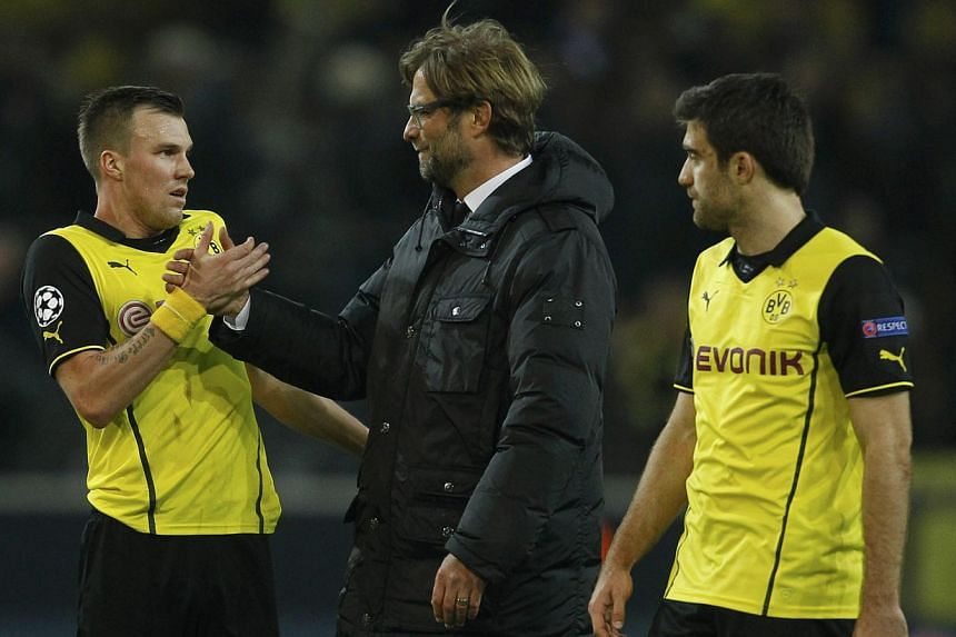 Borussia Dortmund's Kevin Grosskreutz (left), coach Juergen Klopp and Sokratis Papastathopoulos (right) celebrating their team's progress in the Champions League after the match against Zenit St Petersburg in Dortmund on March 19, 2014. -- PHOTO: REU