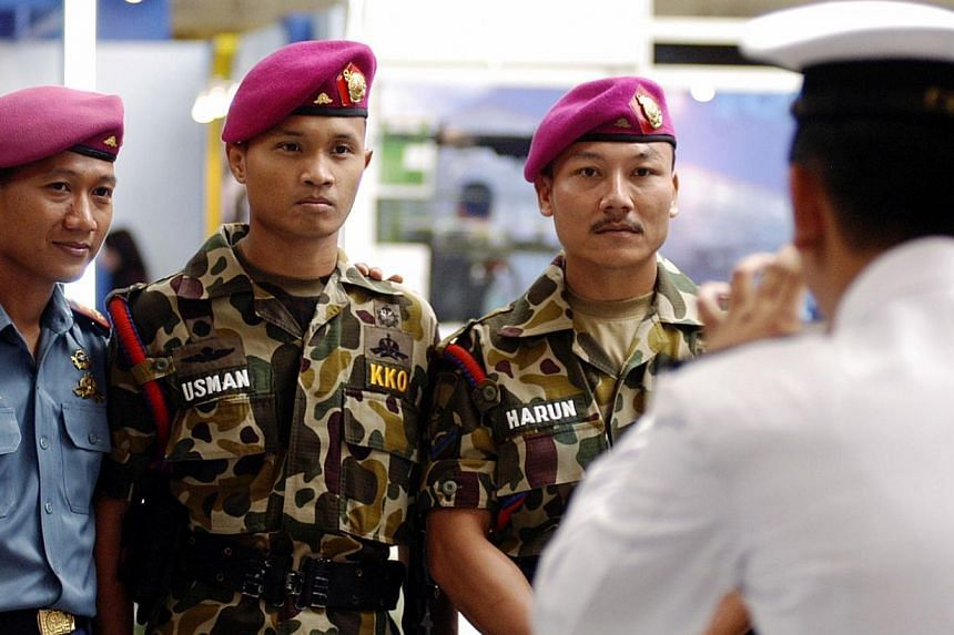 Indonesian soldiers posed for photos with the lookalikes of marines Usman and Harun at the Jakarta International Defence Dialogue exhibition in Jakarta. -- PHOTO: TEMPO