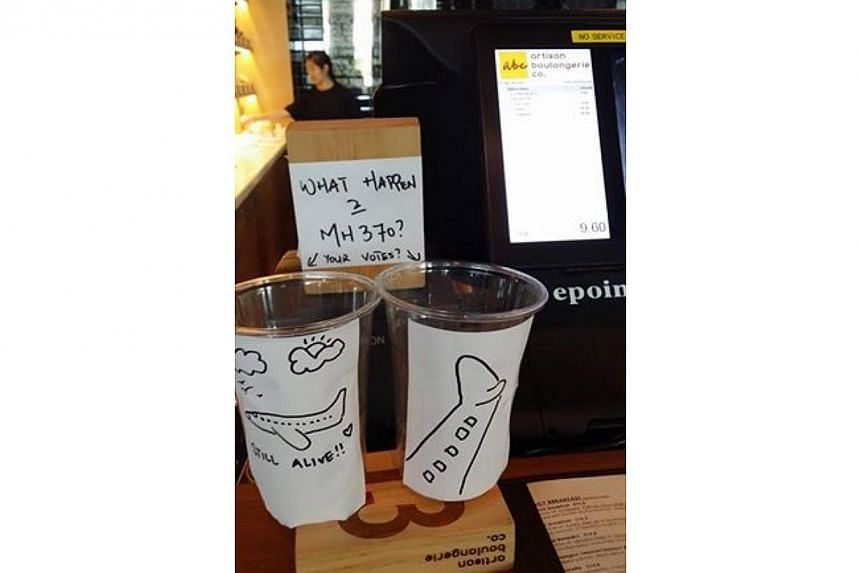 """One cup at the Artisan Boulangerie Compagnie's Asia Square branch showed the tail of a plane diving downwards. The other showed a jet cruising in the clouds with a caption reading """"Still alive!"""" A sign next to them read: """"What happen 2 MH370?""""-"""