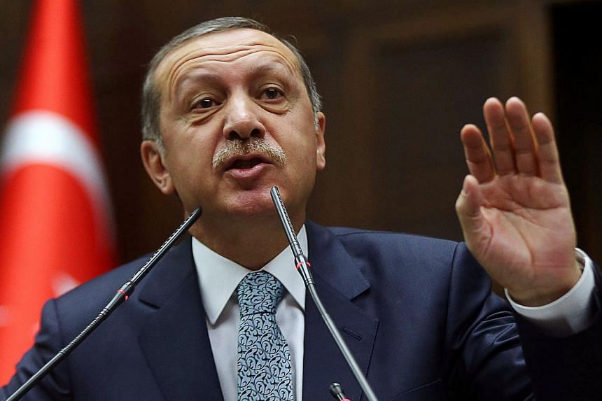 Turkey's Prime Minister Recep Tayyip Erdogan addressing members of his ruling AK Party (AKP) during a session at the Turkish parliament in Ankara on Feb 25, 2014. Mr Erdogan warned on March 20, 2014 that he would eradicate Twitter in the wake of dama