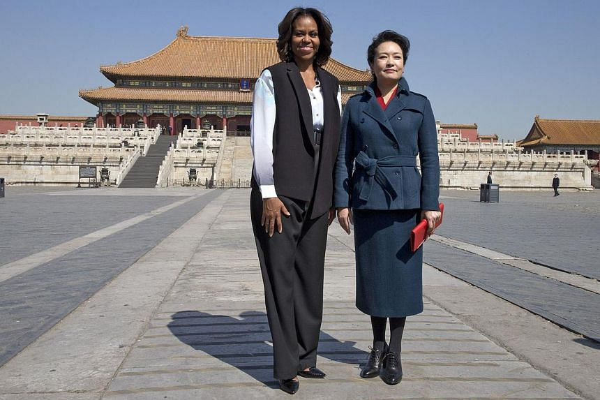 United States First Lady Michelle Obama (left) and Ms Peng Liyuan, wife of Chinese President Xi Jinping pose for photographers as they visit the Forbidden City in Beijing on March 21, 2014. -- PHOTO: AFP