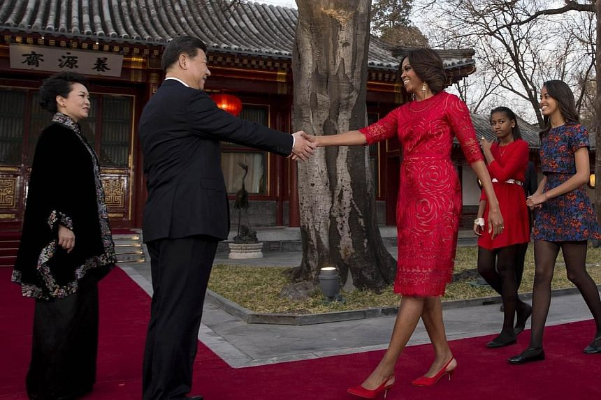 US first lady Michelle Obama, (third right), her daughters Malia (right) and Sasha (second, right) are greeted by Chinese President Xi Jinping (second, left) and his wife Peng Liyuan (left) at a guest house in Beijing on March 21, 2014. -- PHOTO