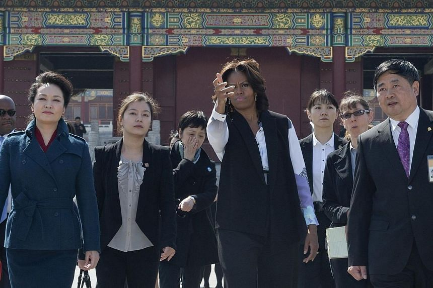 US First Lady Michelle Obama (centre) and Peng Liyuan (left), wife of Chinese President Xi Jinping visit the Forbidden City in Beijing on March 21, 2014. -- PHOTO: AFP
