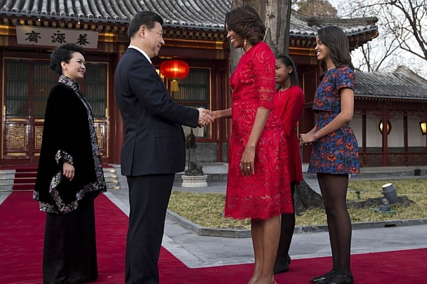 US first lady Michelle Obama, (third, right), her daughters Malia (right) and Sasha (second, right) are greeted by Chinese President Xi Jinping (second, left) and his wife Peng Liyuan (left) at a guest house in Beijing on March 21, 2014. -- PHOT