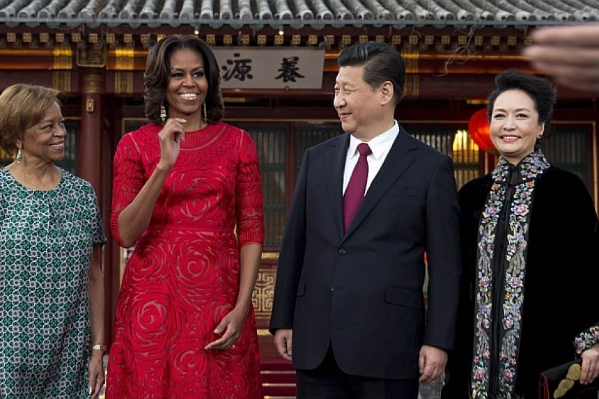 US first lady Michelle Obama (second, left) and her mother Marian Robinson (left) share a light moment with Chinese President Xi Jinping (second, right) and his wife Peng Liyuan after a photograph session at a guest house in Beijing on March 21, 2014