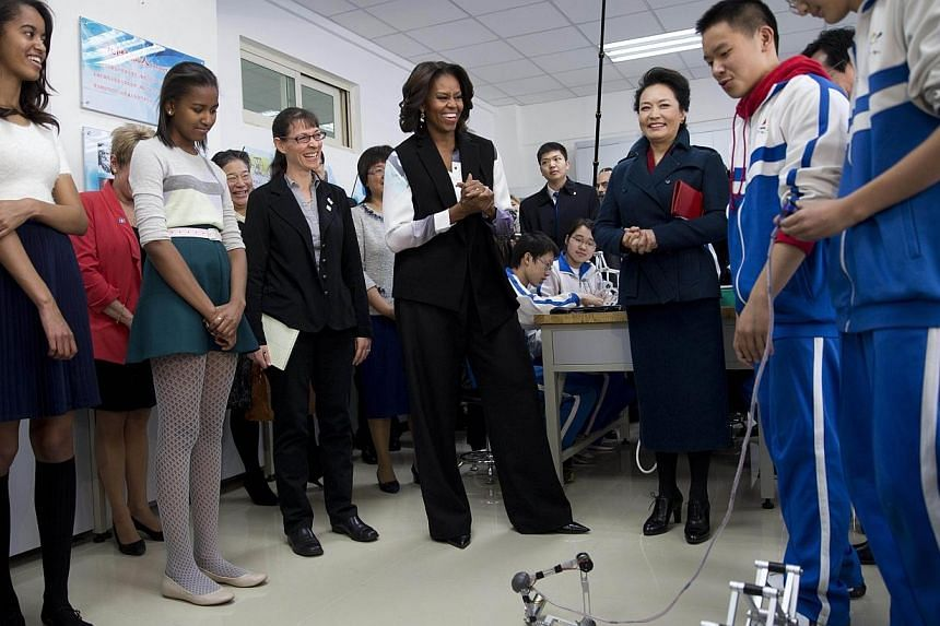 US First Lady Michelle Obama (centre), her daughters Malia (left) and Sasha (second left), accompanied by Peng Liyuan (third right), wife of Chinese President Xi Jinping, look at students demonstrate a remote control mechanical robots at the Beijing