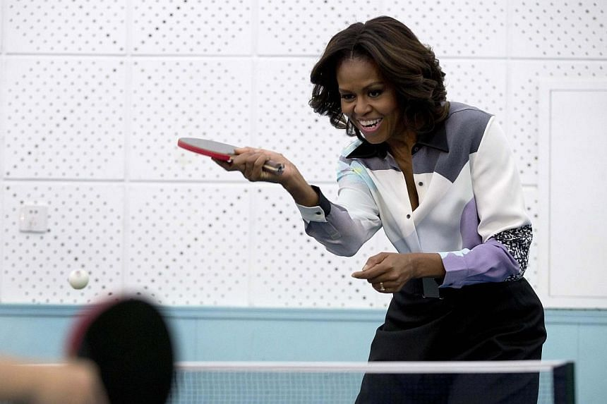 US first lady Michelle Obama plays table tennis during her visit of Beijing Normal School, a school that prepares students for universities abroad, in Beijing on March 21, 2014. -- PHOTO: REUTERS