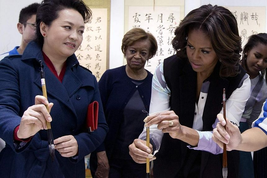 Peng LiyuaN (left), wife of Chinese President Xi Jinping, shows US first lady Michelle Obama how to hold the writing brush as they visit a Chinese traditional calligraphy class at the Beijing Normal School, a school which prepares students for univer