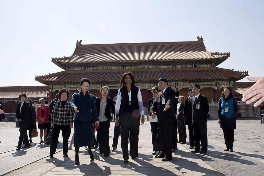 US first lady Michelle Obama (centre) and Peng Liyuan, wife of Chinese President Xi Jinping (centre left), are escorted by officials as they visit Forbidden City in Beijing on March 21, 2014. -- PHOTO: REUTERS
