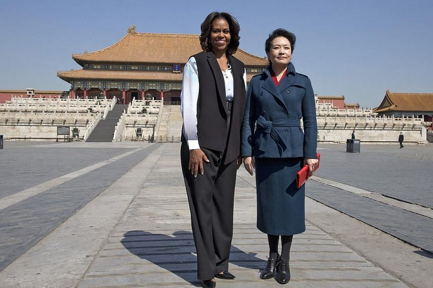 US first lady Michelle Obama (left) and Peng Liyuan, wife of Chinese President Xi Jinping, pose for a photograph as they visit Forbidden City in Beijing on March 21, 2014. -- PHOTO: REUTERS