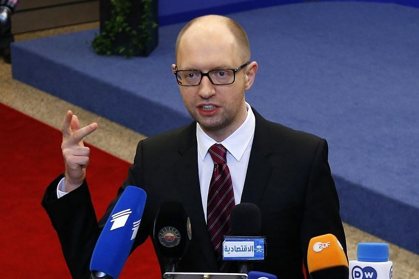 Ukraine's Prime Minister Arseniy Yatsenyuk talks to reporters while leaving a European Union leaders summit in Brussels on March 21, 2014.Yatsenyuk put his country firmly in the Western camp on Friday, March 21, 2014, signing the political prov
