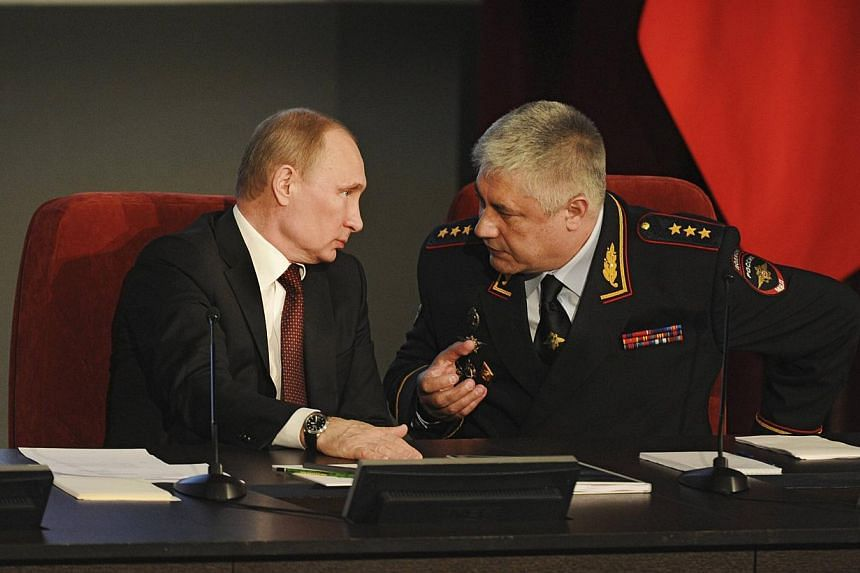 Russian President Vladimir Putin speaks with Interior Minister Vladimir Kolokoltsev during a meeting with Interior Ministry personnel in Moscow, on March 21, 2014. President Putin signed legislation on Friday that completed the process of absorbing C