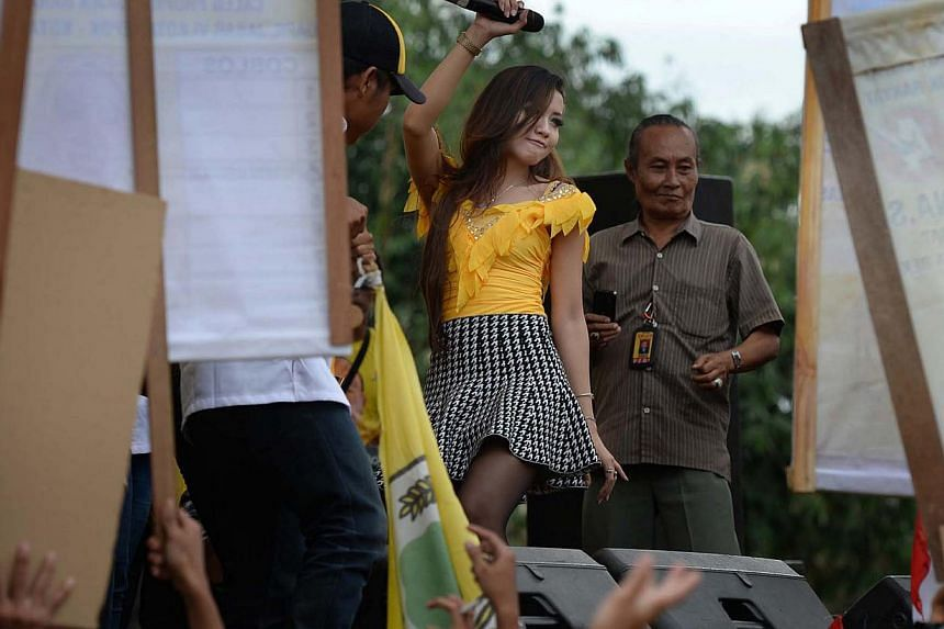 A dangdut performer gyrating to the music at a Golkar rally in Depok, an hour out of Jakarta, on March 21, 2014. The dangdut style of music which blends in Indian, Malay and Arabic elements is very popular in Indonesia and helps pull large crowds to