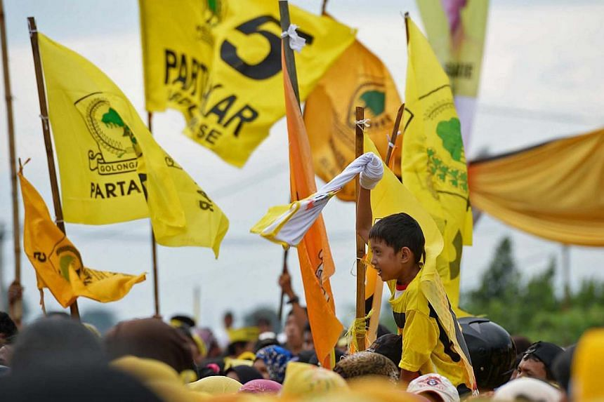 A boy stands out in a sea of flags, waving a T-shirt as the crowd enjoys the Dangdut music, at a Golkar rally in Depok on March 21, 2014. -- PHOTO: Raj Nadarajan