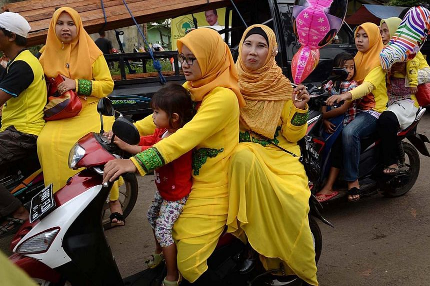 Women dressed in yellow leaving the site of a Golkar rally in Depok on March 21, 2014. -- PHOTO: Raj Nadarajan
