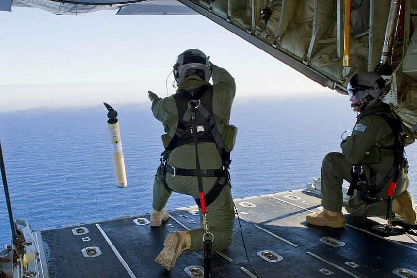 A photo taken on March 20, 2014, shows Royal Australian Air Force Loadmasters, Sergeant Adam Roberts (left) and Flight Sergeant John Mancey (right), preparing to launch a Self Locating Data Marker Buoy from a C-130J Hercules aircraft in the southern
