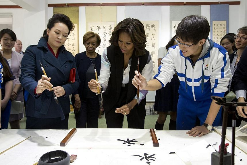 Ms Peng Liyuan (left), wife of Chinese President Xi Jinping, shows United States First Lady Michelle Obama how to hold a writing brush as they visit a Chinese traditional calligraphy class at the Beijing Normal School, a school that prepares students