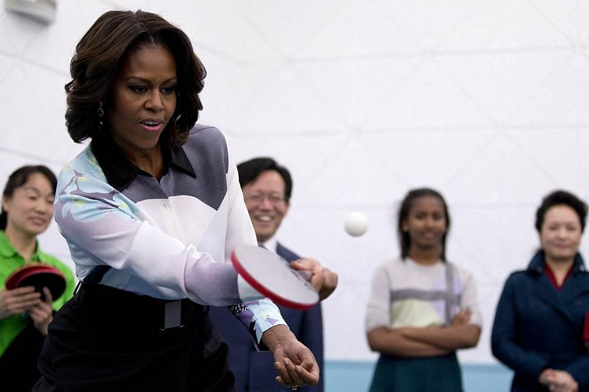 United States First Lady Michelle Obama plays table tennis as Ms Peng Liyuan (right), wife of Chinese President Xi Jinping, looks on during their visit to the Beijing Normal School, a school that prepares students to attend university abroad in Beiji