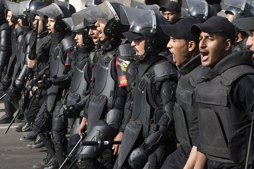 Egyptian riot policemen march forward towards Cairo University on March 19, 2014, as clashes broke out during a protest by Muslim brotherhood students, supporters of ousted president Mohamed Morsi. -- FILE PHOTO: AFP