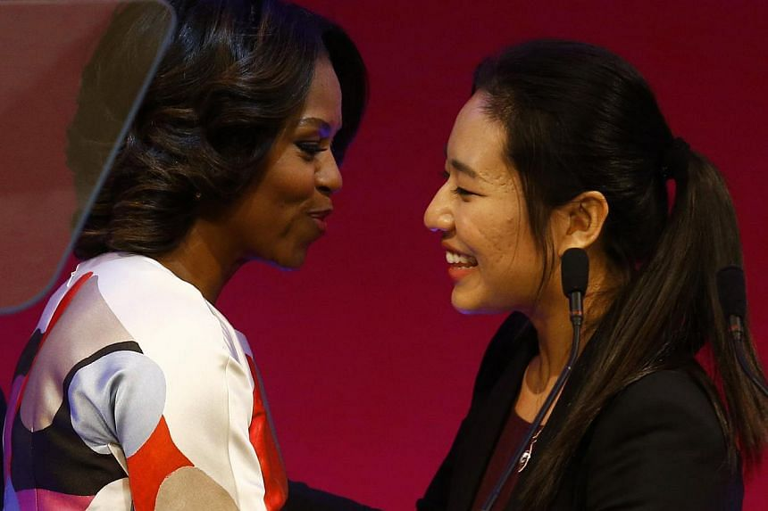 US first lady Michelle Obama (L) is greeted by student Zhu Xuanhao before giving a speech at the Peking University in Beijing on March 22, 2014. -- PHOTO: REUTERS