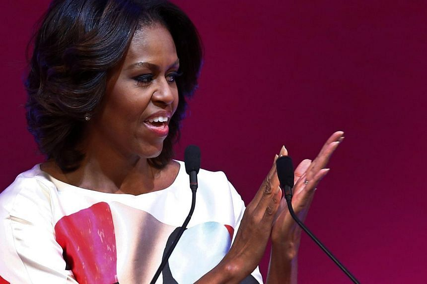US first lady Michelle Obama claps as she gives a speech at the Peking University in Beijing on March 22, 2014. -- PHOTO: REUTERS