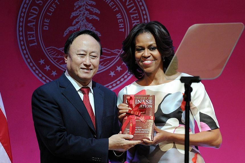 US first lady Michelle Obama (R) receives a book given by Peking University Communist Party Secretary Zhu Shanlu, during her visit at the Peking University in Beijing on March 22, 2014. -- PHOTO: REUTERS