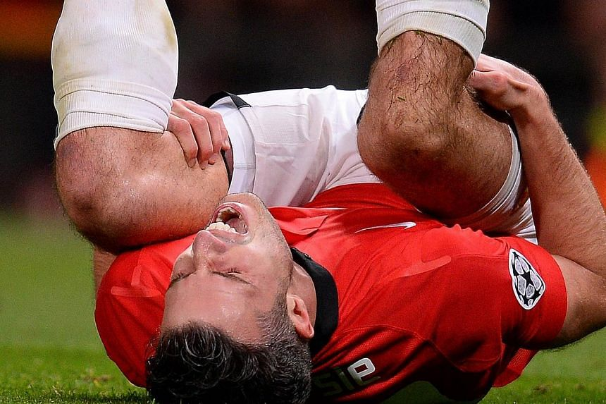 Manchester United's Dutch forward Robin van Persie reacts as he is injured during the Uefa Champions League round of 16 second leg football match between Manchester United and Olympiakos at Old Trafford in Manchester on March 18, 2014. -- PHOTO: AFP