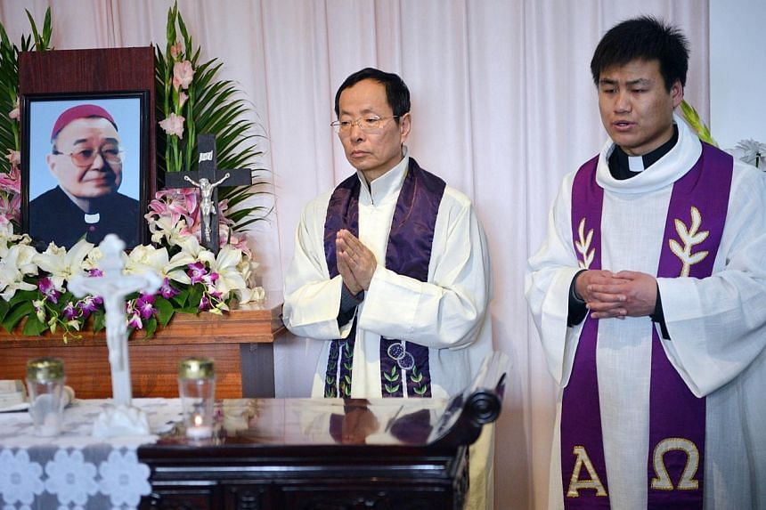 Priests pray for the late head of the underground Catholic Church in Shanghai, Bishop Joseph Fan Zhongliang, at a funeral home in Shanghai on March 18, 2014. Thousands of mourners packed a Shanghai square on Saturday, March 22, 2014, to bid fare