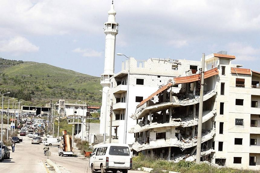 """A damaged building is seen at Husen village in Homs, after soldiers loyal to Syria's President Bashar al-Assad took control of it from rebel fighters, March 21, 2014.A Singaporean man is being investigated for allegedly going to Syria """"with the"""
