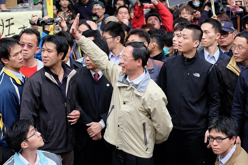 Taiwan Premier Jiang Yi-huah (centre) waves during a visit to meet protesting students outside the parliament as ongoing protests by thousands of people continue for another day outside the parliament in Taipei on March 22, 2014.Jiang said on S