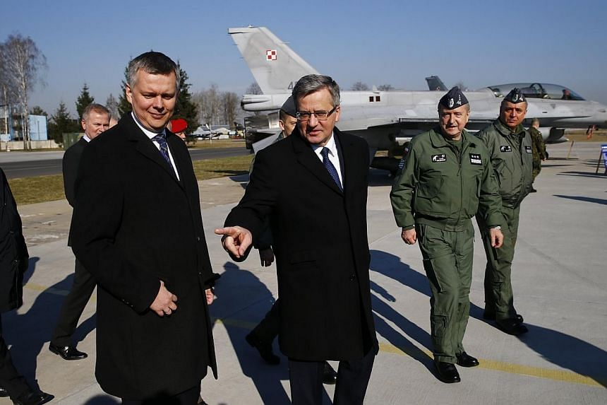 Poland's President Bronislaw Komorowski (centre) and Defence Minister Tomasz Siemoniak (left) talk as they visit the Lask airbase in central Poland on March 11, 2014. The US should increase its military presence in Poland and in other Nato membe