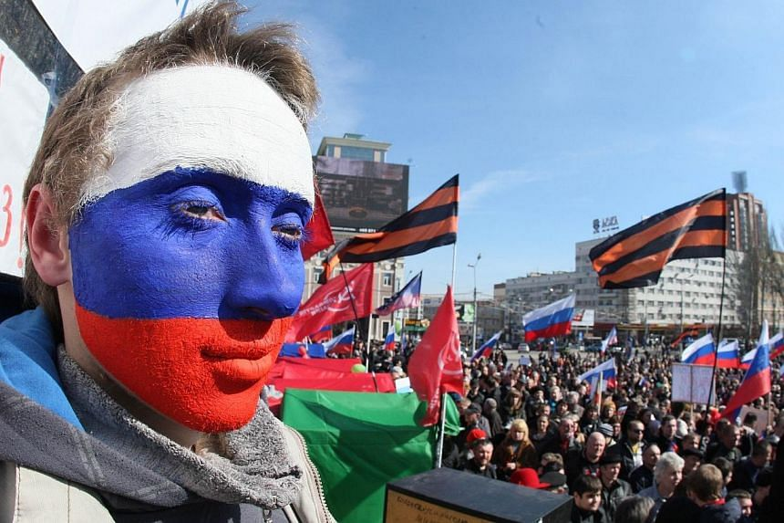 A pro-Russian activist with his face painted in the Russian colours attends a rally in the eastern Ukrainian city of Donetsk on March 22, 2014. About 200 pro-Russian protesters on Saturday, March 22, 2014, stormed a Ukrainian air force base in w