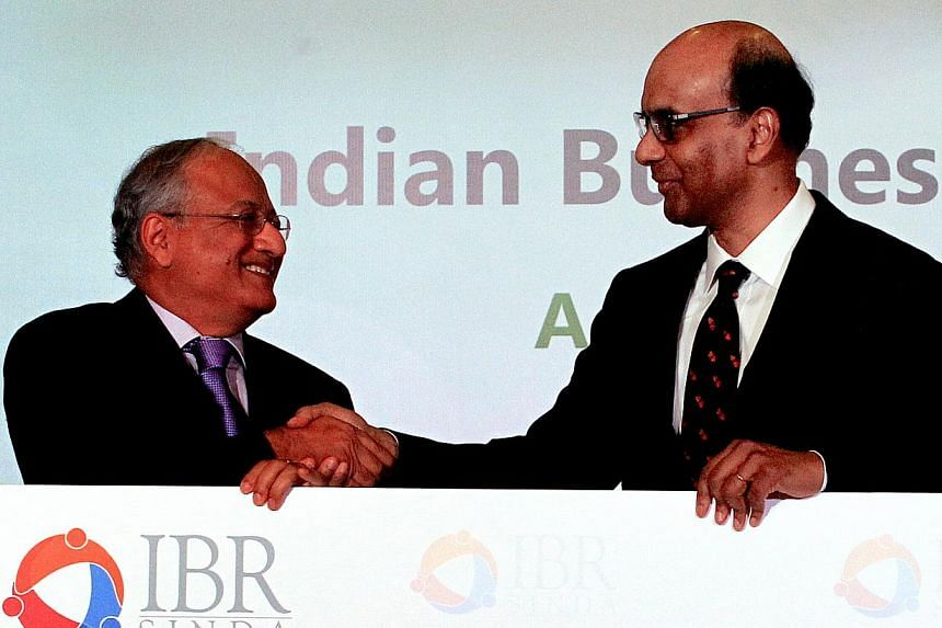DPM Tharman Shanmugaratnam (right) receiving a cheque from Mr Girija Pande, head of Sinda's Indian Business Leaders' Roundtable.