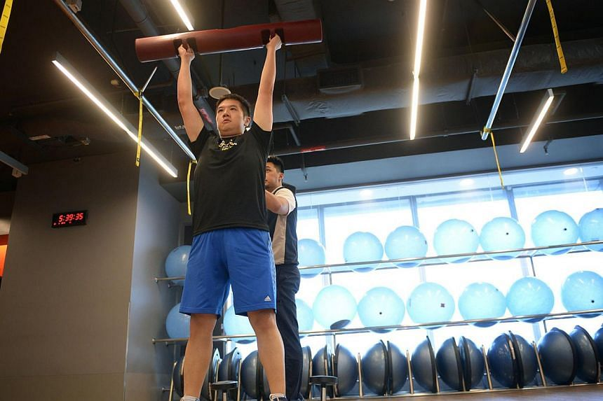Mr Hayden Sum (foreground) during circuit training with personal trainer Terence Chia, 30. -- ST PHOTO: MARK CHEONG
