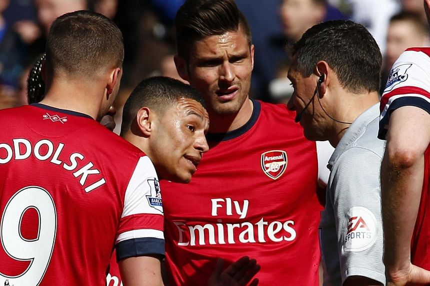 Arsenal's Alex Oxlade-Chamberlain (left) talking to referee Andre Marriner (right) during their English Premier League match against Chelsea at Stamford Bridge in London on March 22, 2014. Arsenal were trailing 2-0 when Mariner gave a penalty and a r
