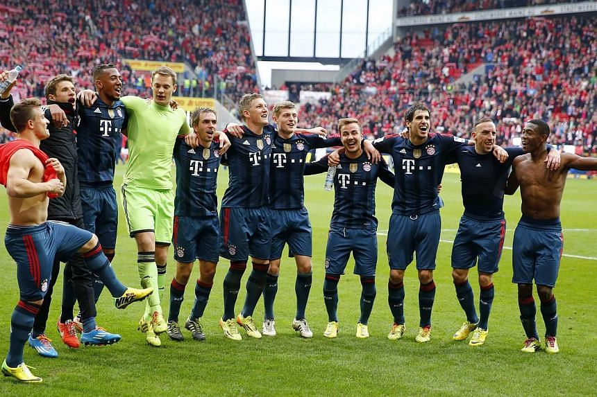 Bayern Munich's players celebrating after their German first division Bundesliga match against FSV Mainz 05 in Mainz, on March 22, 2014. -- PHOTO: REUTERS