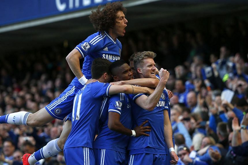 Chelsea's Andre Schurrle (right) celebrating with team mates after scoring a goal against Arsenal during their English Premier League match at Stamford Bridge in London on March 22, 2014. -- PHOTO: REUTERS