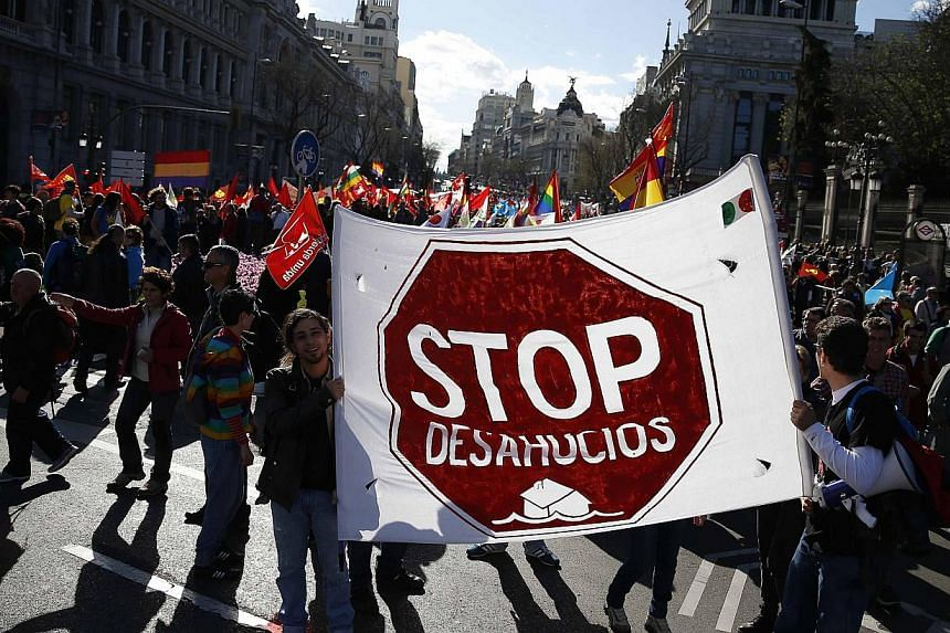 """Anti-austerity demonstrators hold up a sign reading """"Stop Evictions"""" as they take part in a demonstration, which organisers have labelled the """"Marches of Dignity"""", in Madrid on March 22, 2014. -- PHOTO: REUTERS"""