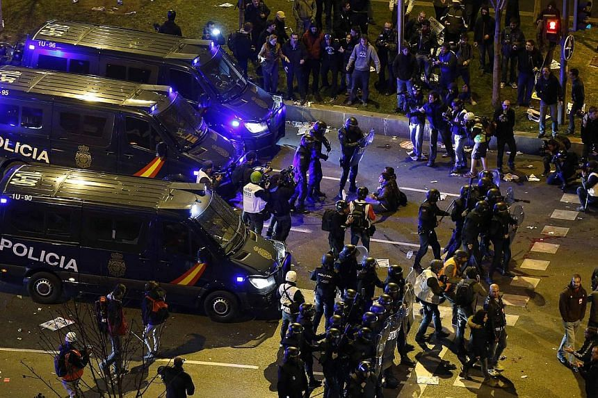 """Riot police confront protesters after disturbances broke out at the end of a demonstration, which organisers have labelled the """"Marches of Dignity"""", in Madrid on March 22, 2014. -- PHOTO: REUTERS"""