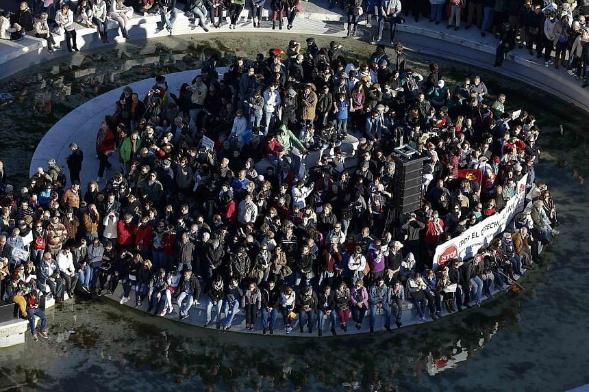 """Anti-austerity demonstrators sit around a fountain in Colon square as they take part in a demonstration, which organisers have labelled the """"Marches of Dignity"""", in Madrid on March 22, 2014. -- PHOTO: REUTERS"""