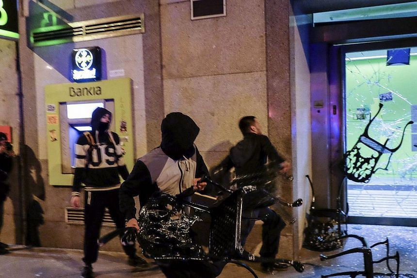 """Demonstrators attack the facade of a Bankia's branch during clashes with police at the end of a march dubbed """"the Marches for Dignity 22-M"""" to protest against austerity in Madrid on March 22, 2014.-- PHOTO: AFP"""