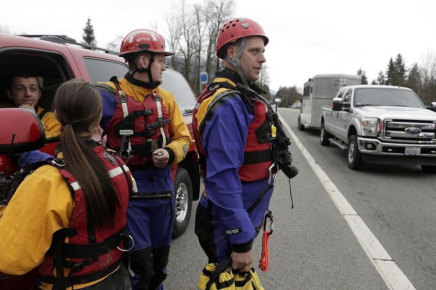 Members of a swift water rescue team look on as a truck pulling a horse trailer drives in the opposite direction of a large mudslide that has blocked Highway 530 near Oso, Washington on March 22, 2014. -- PHOTO: REUTERS